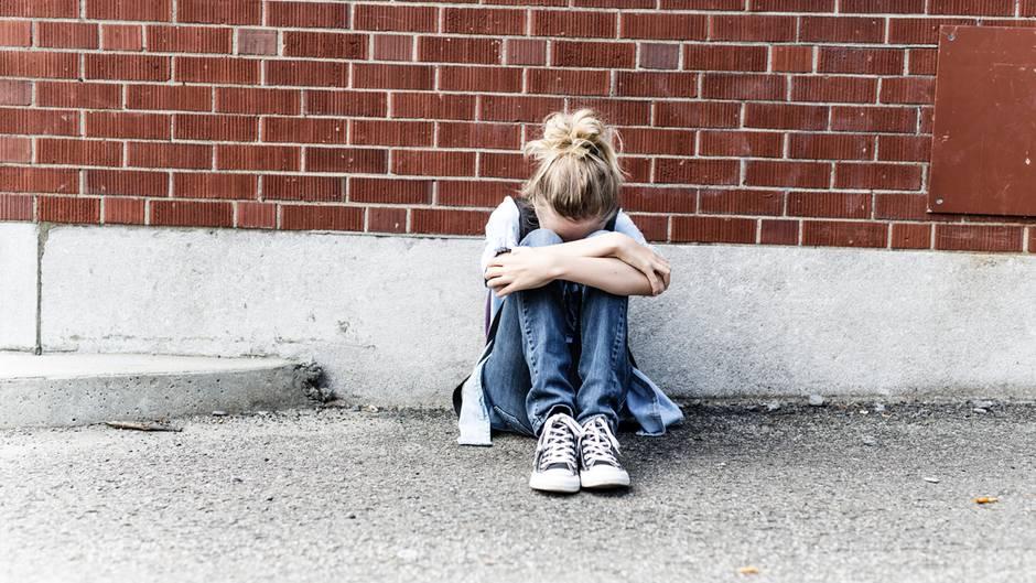 Ein junges Mädchen sitzt vor einer Mauer und weint