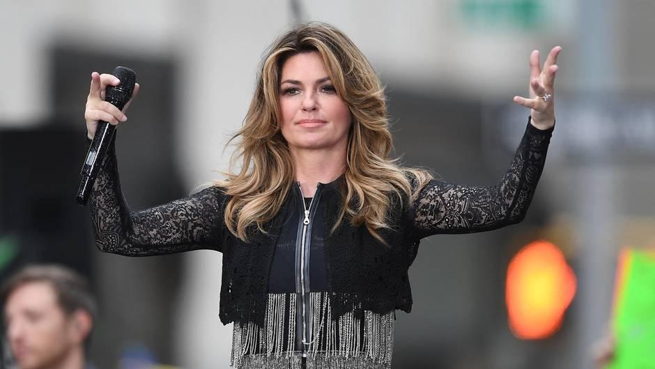 In schwarzer Bolero-Jacke steht Sängerin Shania Twain auf der Bühne, ein Mikro in der rechten Hand, und winkt ins Publikum