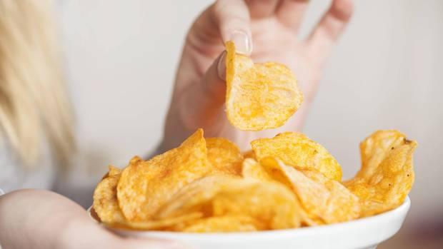 Eine Frau isst Chips aus einer Schale