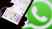 Smartphone vor dem WhatsApp-Logo