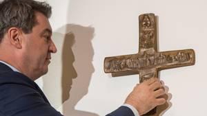 Bayerns Ministerpräsident Markus Söder steht vor einer Wand und hängt ein Kreuz auf. Er ist im Profil zu sehen und trägt Anzug