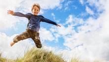 Ein Junge springt durch eine Düne