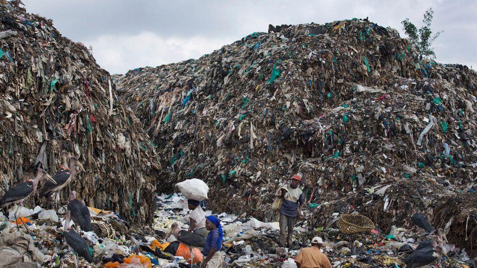 Menschen durchsuchen im Dandora Slum in Nairobi einen Müllberg nach wiederverwertbaren Gegenständen.