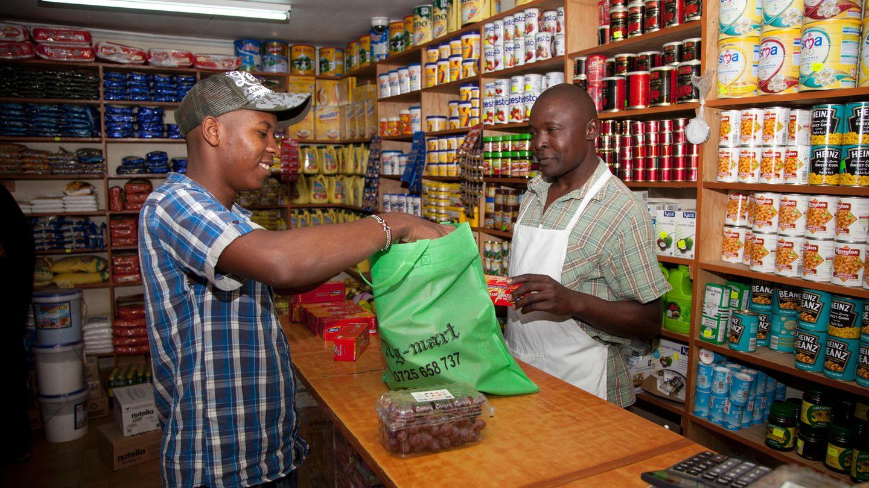 Kenia, Nairobi: Ein Mann packt seine Einkäufe in eine Stofftüte.