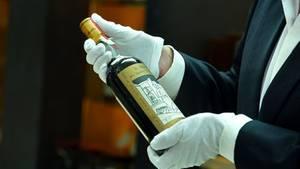 Mann inspiziert Flasche des Whiskeys The Macallan