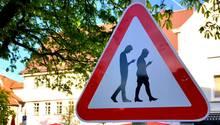 Verkehrsschild rotes Dreieck mit zwei Figuren, die beim Gehen auf das Smartphone schauen
