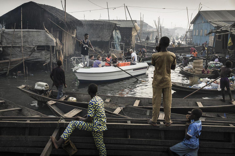 """Fotograf: Jesco Denzel    24. Februar 2017    1. Preis im Segment """"Einzelfotos""""  Ein Boot mit Touristen wird durch die Makoko-Siedlung manövriert. Das frühere Fischerdorf am Ufer der Lagune von Lagos, Nigeria, hat sich zu einem enormen Wasser-Slum entwickelt.    Makoko hat rund 150.000 Einwohner, die meisten Familien leben hier schon seit Generationen. Aber Lagos wächst schnell, da ist Bauland sehr gefragt - und Luxusimmobilien am Ufer der Lagune sind begehrt. Darum versucht man, Gemeinschaften wie Makoko zu vertreiben, damit Apartments gebaut werden können: Wohnungen für die Reichen. Da die Regierung diese Gemeinschaften als informelle Siedlungen betrachtet, dürfen sie geräumt werden, ohne den Einwohnern einen Ersatz anzubieten. Durch die Vertreibung von der """"Waterfront"""" verlieren sie ihre Existenz."""