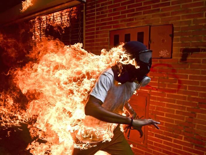 """Fotograf: Ronaldo Schemidt     3. Mai 2017    World Press Photo des Jahres     1. Preis im Segment """"Einzelfotos""""  José Víctor Salazar Balza (28) gerät in Brand bei gewaltsamen Auseinandersetzungen mit der Bereitschaftspolizei, während einer Kundgebung gegen die vom Präsidenten Maduro angekündigte Reform der Staatsordnung, in Caracas, Venezuela.    Maduro wollte das von der Opposition dominierte Parlament durch eine verfassunggebende Versammlung ersetzen und sich damit die gesetzgeberischen Befugnisse faktisch selbst sichern. Oppositionsführer riefen zu Massenprotesten auf, um vorgezogene Präsidentschaftswahlen zu verlangen. Am 3. Mai kam es zu Ausschreitungen zwischen Demonstranten und der Nationalgarde. Die Demonstranten (viele mit Kapuzen, Masken oder Gasmasken) zündeten Brandsätze an und warfen mit Steinen. Balza geriet in Brand, als der Tank eines Motorrads explodierte. Er überlebte mit Verbrennungen ersten und zweiten Grades."""