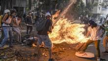 """Fotograf: Juan Barreto    3. Mai 2017    3. Preis im Segment """"Serien""""  Bei Protesten gegen den venezolanischen Präsidenten Maduro gerät José Víctor Salazar Balza (28) in Brand, nachdem der Tank eines Motorrads explodiert ist.    Gewaltsame Ausschreitungen zwischen Demonstranten und der Nationalgarde waren ausgebrochen. Dem Anschein nach wurde das Motorrad eines Nationalgardisten von Demonstranten zerstört. Manchen der unterschiedlichen Berichte über den Vorfall zufolge löste ein von Demonstranten auf den Tank geworfenes Objekt die Explosion aus. Anderen Berichten zufolge fing Balzas Kleidung so leicht Feuer, weil diese durch einen von ihm selbst oder einem anderen Demonstranten mitgeführten Sprengsatz mit Benzin getränkt war.    Balza überlebte den Vorfall trotz schwerer Verbrennungen an über 70 Prozent seines Körpers.    Ein anderes Bild des brennenden Balza wurde zum World Press Photo 2018 gewählt. (Es ist Bild 1 dieser Fotostrecke.)"""