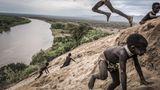 Fotograf: Fausto Podavini     24. Juli 2011 - 24. November 2017    2. Preis     Der Gibe-III-Staudamm im Omo-Fluss in Äthiopien hat nicht nur Auswirkungen für die Bewohner des Omo-Tals, sondern auch auf die Anwohner des Turkana-Sees in Kenia (in den der Omo einmündet). In diesem Tal leben Menschen acht verschiedener Ethnizitäten in einem empfindlichen Gleichgewicht mit der Umwelt. Für ihre Lebensmittelversorgung sind sie auf den Fluss angewiesen.    Die äthiopische Regierung sieht diesen Damm als gewinnbringende Wasserkraftanlage, Quelle von Wasser für die großflächige Landwirtschaft und als Touristen-Attraktion und bestreitet Vorwürfe über die negativen Umweltauswirkungen. Kritiker weisen auf die abnehmende Biodiversität, den sinkenden Wasserstand im Turkana-See, die geringeren Ablagerungen von fruchtbarem Boden durch die jährlichen Überschwemmungen und die Vertreibung traditioneller Völker hin.    Der Fotograf besuchte das Omo-Tal, um mit der Fotostrecke einen gedanklichen Anstoß zu geben, wie Investitionen das Gleichgewicht von Mensch und Umwelt gefährden können. In dieser Szene spielen indigene Karo-Kinder im Sand am Ufer des Omo-Flusses. Die Karo sind auf den Fluss angewiesen: auf Fisch und auf die in dem fruchtbaren Überschwemmungsboden angebauten Nutzpflanzen. Der Wald im Hintergrund wurde abgeholzt, um Platz für den Baumwollanbau zu schaffen ...