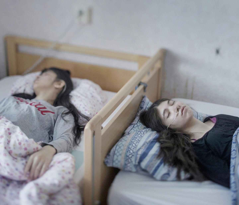 """Fotograf: Magnus Wennman     2. März 2017    1. Preis im Segment """"Einzelfotos""""  Djeneta (rechts) liegt seit zweieinhalb Jahren in komaähnlichem Zustand im Bett, ihre Schwester Ibadeta seit über sechs Monaten. Sie leiden unter uppgivenhetssyndrom (Resignation Syndrome), in Horndal, Schweden.    Djeneta und Ibadeta sind Roma-Flüchtlinge aus dem Kosovo. Am Resignation Syndrome (RS) Erkrankte sind passiv, unbeweglich, stumm, unfähig zu essen und zu trinken, inkontinent und reagieren nicht auf physische Reize. Die Erkrankung scheint nur unter Flüchtlingen in Schweden vorzukommen. Auch wenn die Ursachen rätselhaft sind, halten die meisten Fachleute ein Trauma für einen bedeutenden Auslöser, neben einer Reaktion auf Stress und Depression. Völlig unklar ist auch, warum solche Krankheitsfälle nur in Schweden auftreten. Bisher sind nur Flüchtlingskinder von 7 bis 19 Jahren, hauptsächlich aus der ehemaligen Sowjetunion und dem früheren Jugoslawien, von RS betroffen. Bei vielen trat das Syndrom nach der Ablehnung des Asylantrags auf. Als Heilmittel wird oft vorgeschlagen, den Familien der Erkrankten eine Aufenthaltsgenehmigung zu gewähren."""