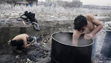 """Fotograf: Francesco Pistilli     12. -17. Januar 2017    3. Preis im Segment """"Serien""""  Durch die faktische Schließung der Balkan-Route in die EU strandeten Tausende von Flüchtlingen auf der Suche nach einem neuen Leben in Europa in Serbien. Viele verbrachten den eisigen Winter in baufälligen Lagerhäusern hinter Belgrads Hauptbahnhof. Nach UNHCR-Angaben stieg die Zahl der Flüchtlinge in Serbien von 2000 im Juni 2016 bis zum Jahresende auf über 7000 an. Davon waren rund 85 Prozent in staatlichen Einrichtungen untergebracht, die meisten anderen schliefen in Belgrad auf der Straße.    Hier waschen sich zwei afghanische Flüchtlinge in Belgrad im Freien."""