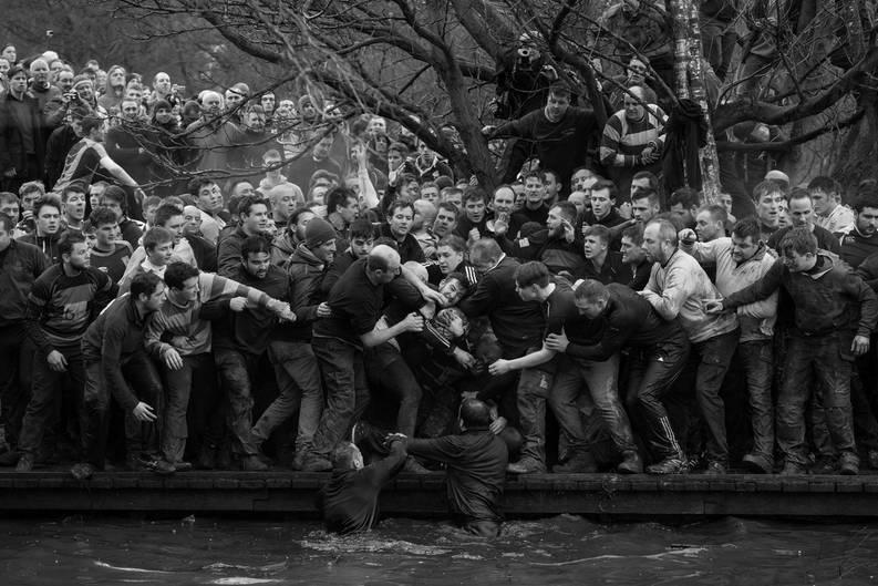 """Fotograf: Oliver Scarff     28. Februar 2017    1. Preis im Segment """"Einzelfotos""""  Die Spieler der beiden gegnerischen Mannschaften, Up'ards and Down'ards, kämpfen um den Ball beim historischen Shrovetide-Fußballspiel in Ashbourne, Derbyshire, Vereinigtes Königreich.    Das Spiel wird von Hunderten Teilnehmern am Faschingsdienstag und am Aschermittwoch jeweils acht Stunden lang ausgetragen. Welcher Mannschaft man angehört, hängt davon ab, an welcher Seite des Henmore-Flusses man geboren wurde: Die Up'ards nördlich, die Down'ards südlich des Flusses. Um ein Tor zu erzielen, muss der Ball dreimal den Mühlstein in einer der drei Meilen voneinander entfernten Steinpyramiden berühren. Regeln gibt es so gut wie keine, nur die historische Regel, dass die Spieler ihre Gegner nicht umbringen dürfen, sowie die modernere Regel, dass der Ball nicht in Taschen, Rucksäcken oder motorisierten Fahrzeugen transportiert werden darf. Der Überlieferung zufolge wird """"Royal Shrovetide Football"""" seit dem 17. Jahrhundert in Ashbourne gespielt."""