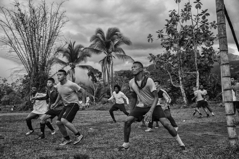 """Fotograf: Juan D. Arredondo     16.-25. September 2017    2. Preis im Segment """"Serien""""  Ehemalige FARC-Guerillas, die nach einem Konflikt von über 50 Jahren die Waffen niedergelegt haben, zogen aus Dschungelkamps in Übergangszonen im ganzen Land um, wo sie demobilisiert werden und lernen, wieder im zivilen Leben Tritt zu fassen. Viele von ihnen beteiligen sich an Fußballspielen mit Mannschaften, die sowohl aus Opfern des Konflikts als auch aus kolumbianischen Soldaten bestehen. Es ist geplant, aus den besten Spielern der Mannschaften aus den Übergangszonen einen """"La Paz""""-(Friedens-)Fußballverein zusammenzustellen.    Hier zu sehen ist ein Freundschaftsspiel zwischen Soldaten der kolumbianischen Nationalarmee und einer FARC-Mannschaft in Vegaez, Antioquia."""