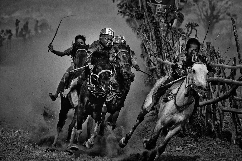 """Fotograf: Alain Schroeder     17.-25. September 2017    1. Preis im Segment """"Serien""""  Kinder-Jockeys reiten ohne Sattel, barfuß und ohne ordentliche Schutzausrüstung auf kleinen Pferden, während der Maen-Jaran-Pferderennen auf der Insel Sumbawa, Indonesien. Die Maen-Jaran-Tradition wird von einer Generation zur nächsten weitergegeben. Früher war es ein Zeitvertreib, mit dem man eine gute Ernte feierte. Im 20. Jahrhundert wurden die Pferderennen auf Sumbawa dann zum Zuschauersport zur Unterhaltung niederländischer Amtsträger.    Die fünf bis zehn Jahre alten Jungen, die fünf bis sechsmal täglich auf ihre kleinen Pferde steigen, erreichen Geschwindigkeiten von bis zu 80 Stundenkilometern. Die Sieger erhalten Geldpreise, die Teilnehmer verdienen 3,50 Euro bis 7 Euro pro Rennen.    Hier zu sehen ist eine Szene aus einem der vielen Rennen an diesem Tag."""