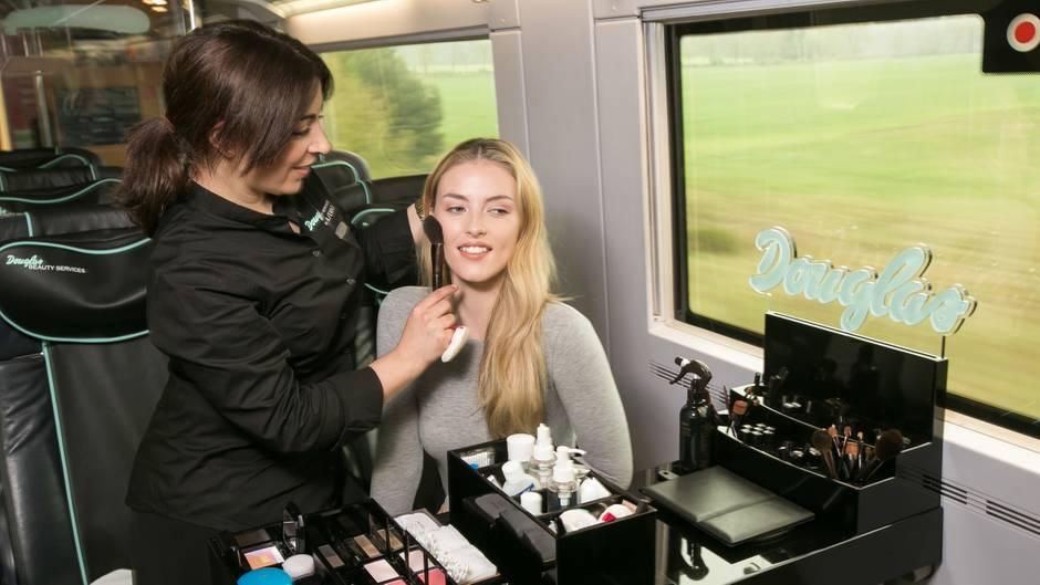 Eine Frau lässt sich im ICE von einer Douglas-Kosmetikerin schminken
