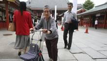 Ältere japanische Frau mit Rollator