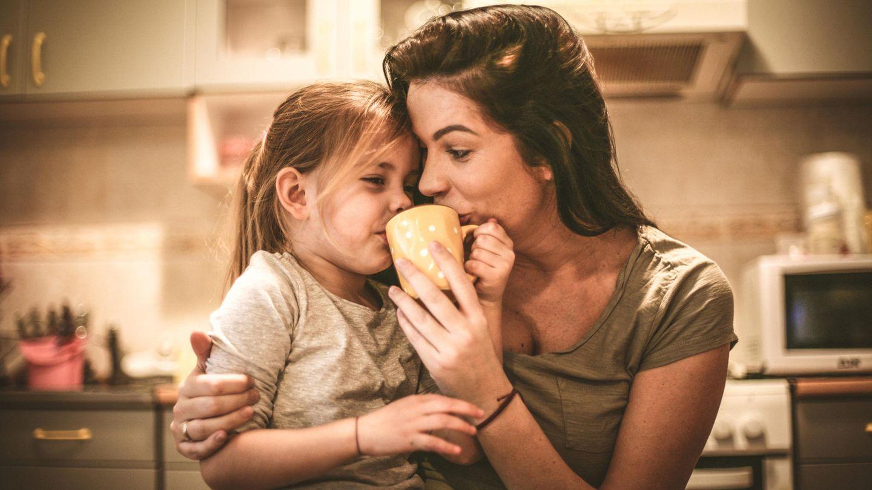 Ein Mädchen sitzt auf dem Schoß seiner Mutter und trinkt Tee