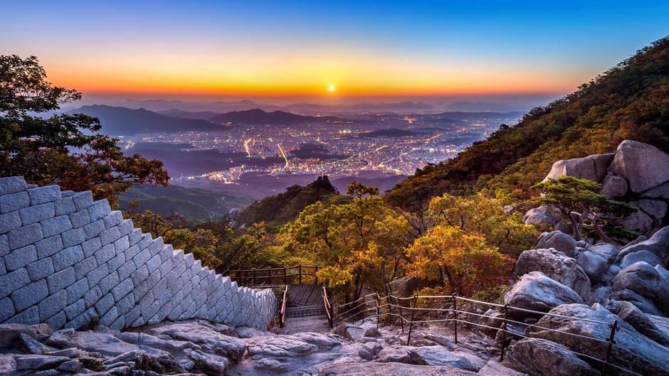Wandern ist in Südkorea Volksport Nummer ein: Sonnenaufgang am Baegundae Peak and Bukhansan-Nationalpark Mountain mit Seoul im Hintergrund.