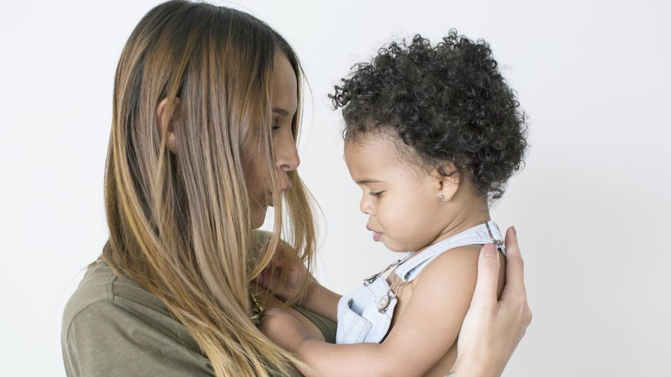 Eine weiße Mutter mit einem schwarzen Baby im Arm