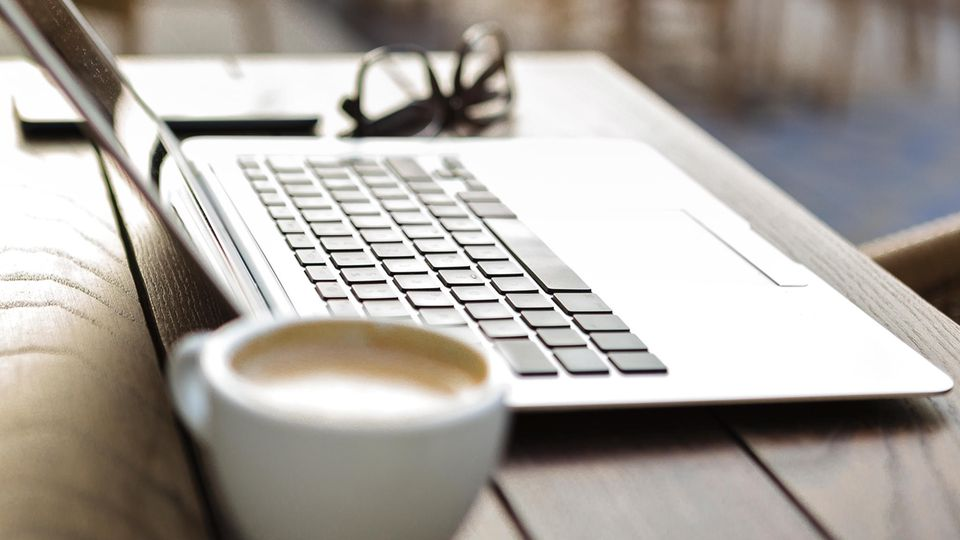 Kaffeetasse vor einem Laptop und einer Brille