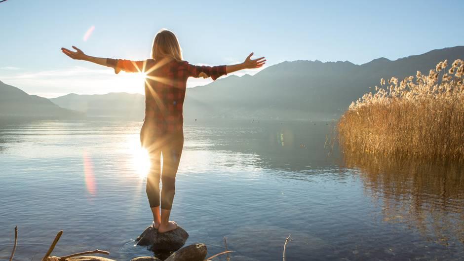 Eine Frau steht am See und entspannt