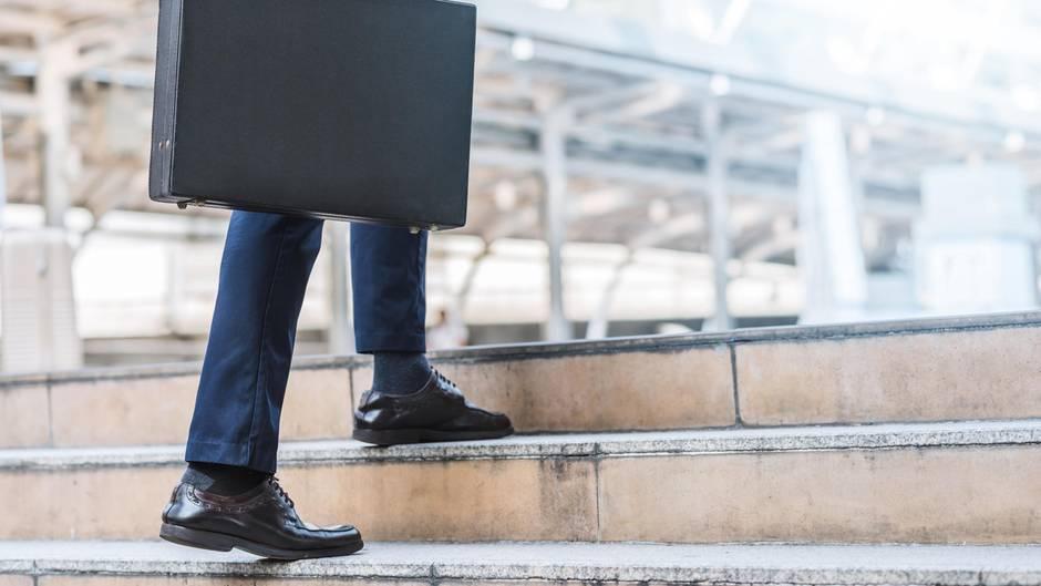 Ein Mann im dunklen Anzug und mit Aktenkoffer steigt eine Treppe empor