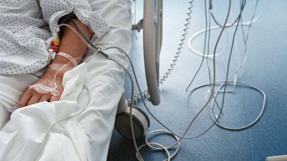Ein Patient mit einer Infusion im Arm liegt in einem Krankenhausbett