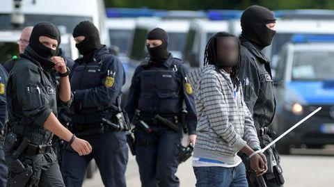 Polizei-Großeinsatz in einem Asylbewerberheim in Ellwangen: Verdächtiger wird abgeführt