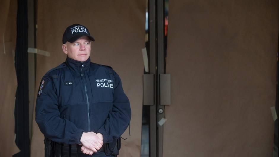 Ein Polizist steht vor einer mit blickdichtem Papier beklebten Glastür.