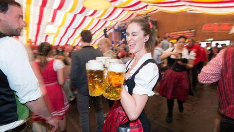 Eine Kellnerin mit Bierkrügen inmitten einer Menschenmenge beim Stuttgarter Frühlingsfest.
