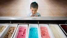Ein kleiner Junge steht vor bunten Eissorten