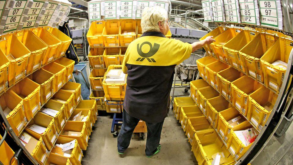 Eine Mitarbeiterin der Deutschen Post sortiert Großbriefe in einem Briefzentrum