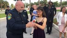 Ein Polizist bindet einer Schülerin ein Blumensträußchen ans Handgelenk