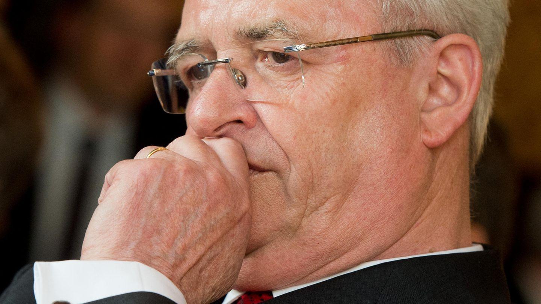 Ex-VW-Chef Martin Winterkorn schaut besorgt und hält sich die linke Faust vor den Mund. Er trägt Anzug und randlose Brille