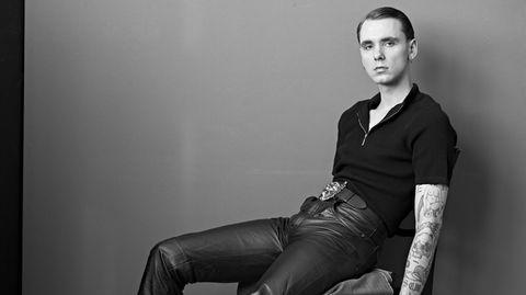 Drangsal in schwarzer Kleidung lässig auf einem Stuhl sitzend