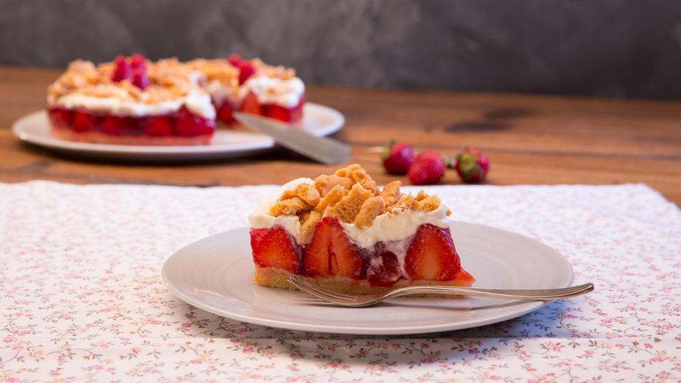Ein Stück Erdbeerstreuselkuchen auf einem Teller.