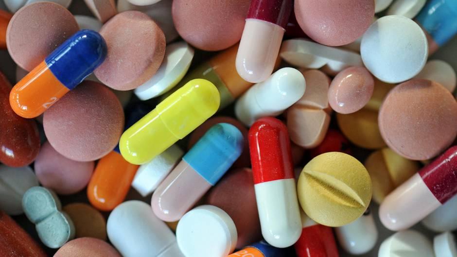 Verschiedene Pillen und Tabletten liegen auf einem Teller
