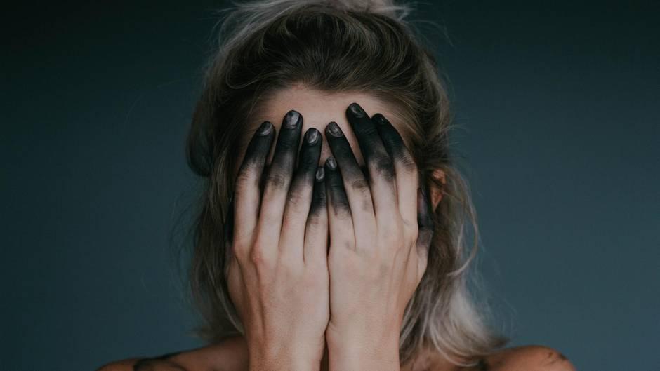 Frau mit Händen vor dem Gesicht