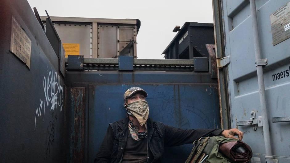 Zuch sitzt in einem Deepwell-Güterzuganhänger. Neben den geladenen Containern finden sich ein paar Meter Platz um es sich gemütlich zu machen und unbemerkt mitzufahren.