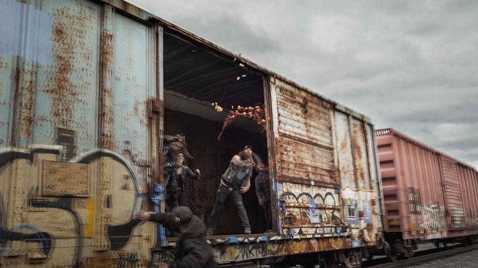 Mit Tomatensauce und Orangenschalen werfen Hobos während der Railroad Days in Dunsmuir, Kalifornien, aus einem abfahrenden Zug
