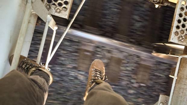 Tamina-Florentine Zuch fotografiert ihre Füße, während sie auf das Dach des Getreidewaggons steigt. Der Schotter unter ihr verschwimmt