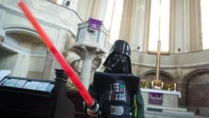 Ein Mann im Darth-Vader-Kostüm und einem Laserschwert in der Hand