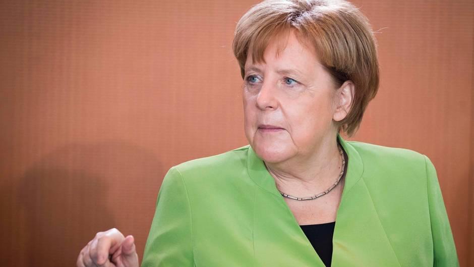 In einem frühlingsgrünen Blazer sitzt Bundeskanzlerin Angela Merkel am Kabinettstisch und gestikuliert mit der rechten Hand
