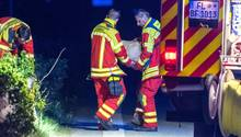 Zwei Männer in Feuerwehr-Kleidung tragen einen in Papier gehüllten, fußballgroßen Stein von der Unfallstelle auf der A7