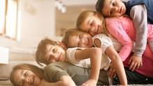 Kinder liegen übereinandergestapelt auf dem Teppich