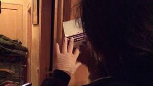 Eine Polizistin steht vor einer offenen Wohnungstür. Mit Gummihandschuhen an den Händen macht sie sich Notizen