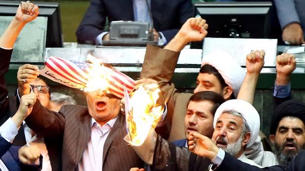 Parlamentarier im Iran verbrennen eine US-Flagge aus Papier