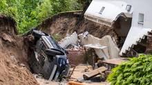 Ein Auto liegt in Hamburg-Lohbrügge in einer Senke die nach heftigem Regen entstanden ist