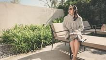 Eine Frau in Australien sitzt im dicken Wintermantel in der Sonne